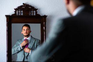 Boda en Aldeanueva del Camino de Sonia y Samuel realizada por el fotógrafo de bodas Johnny García. Samuel se atusa la corbata delante del espejo.