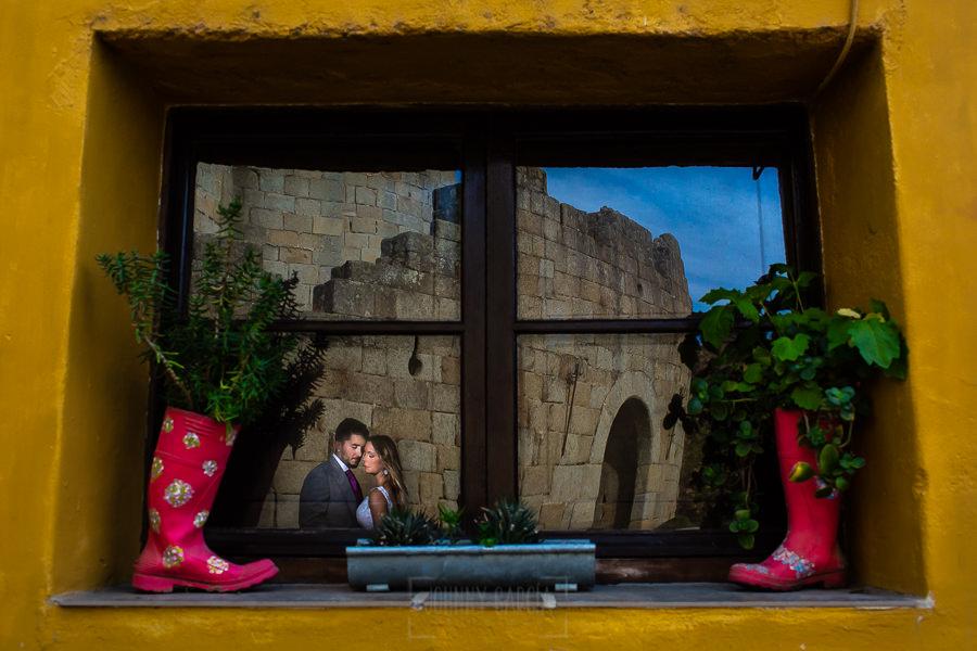 Boda en Aldeanueva del Camino de Sonia y Samuel realizada por el fotógrafo de bodas Johnny García. Una foto de la pareja reflejada en la ventana de una casa.