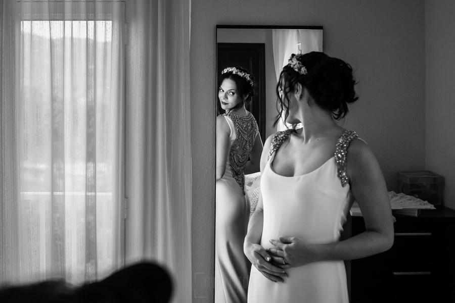 Boda en el Rincón de Castilla de Isa y Juan, realizada por el fotógrafo de bodas en Béjar Johnny García, la novia se mira al espejo para ver su vestido por detrás.