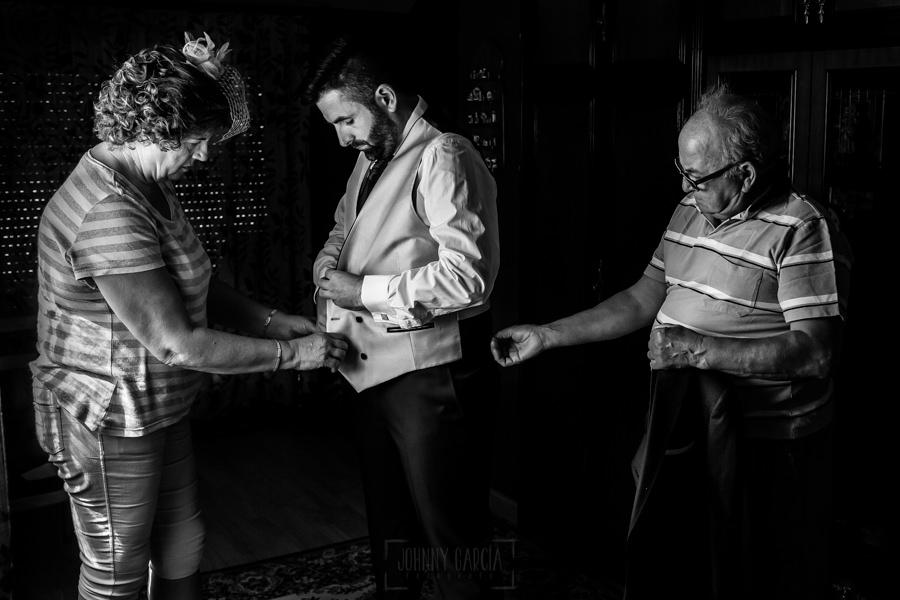 Boda en el Rincón de Castilla de Isa y Juan, realizada por el fotógrafo de bodas en Béjar Johnny García, Los padres de Juan le ayudan a vestirse.