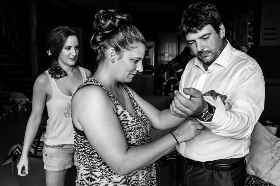 Boda en Segura de Toro de Araceli y César, captada fotográficamente por elfotógrafo de bodas en Cáceres Johnny García, las hermanas de César le ayudan con los gemelos de la camisa.