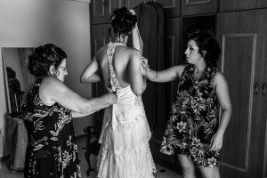 Boda en Segura de Toro de Araceli y César, captada fotográficamente por elfotógrafo de bodas en Cáceres Johnny García, Araceli se viste con la ayuda de su madre y hermana.