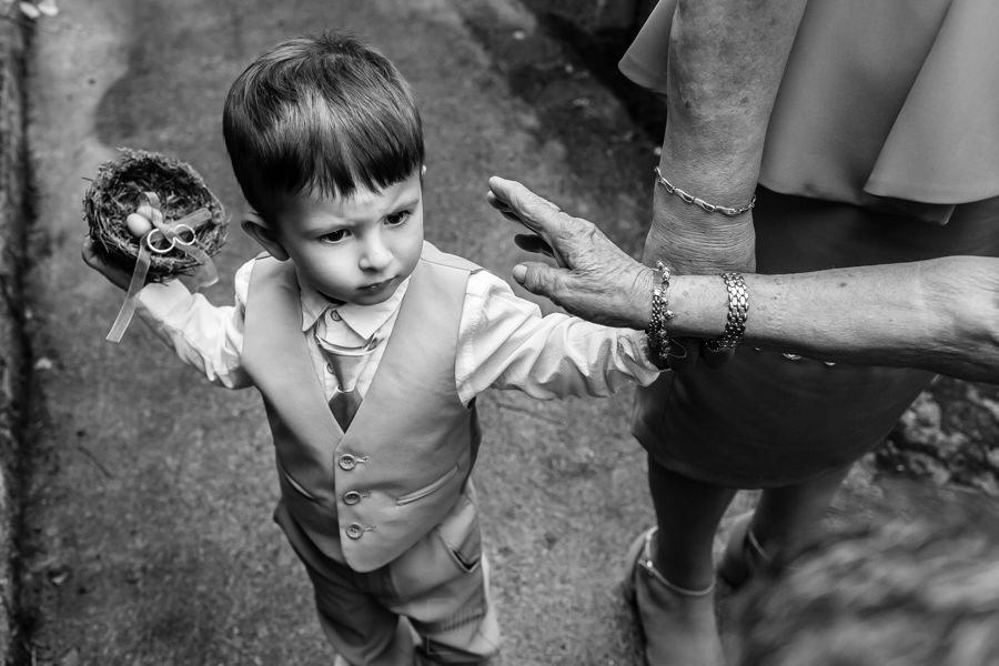 Boda en Segura de Toro de Araceli y César, captada fotográficamente por elfotógrafo de bodas en Cáceres Johnny García, el pequeño que lleva las alianzas no deja que nadie las toque.