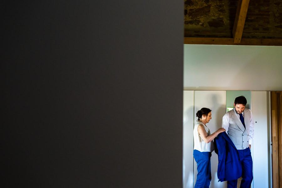 Boda en Hervás de Yolanda e Ignacio, foto realizada por el fotógrafo de bodas en Cáceres Johnny García. La madre del novio le ayuda a vestirse.