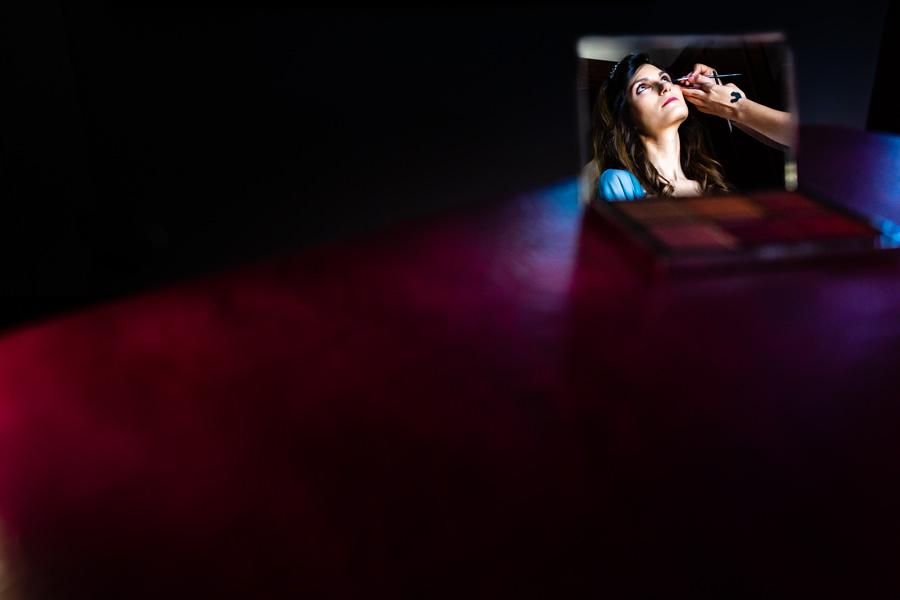 Boda en Hervás de Yolanda e Ignacio, foto realizada por el fotógrafo de bodas en Cáceres Johnny García. Retrato de Yolanda reflejada en un espejo mientras la maquillan.