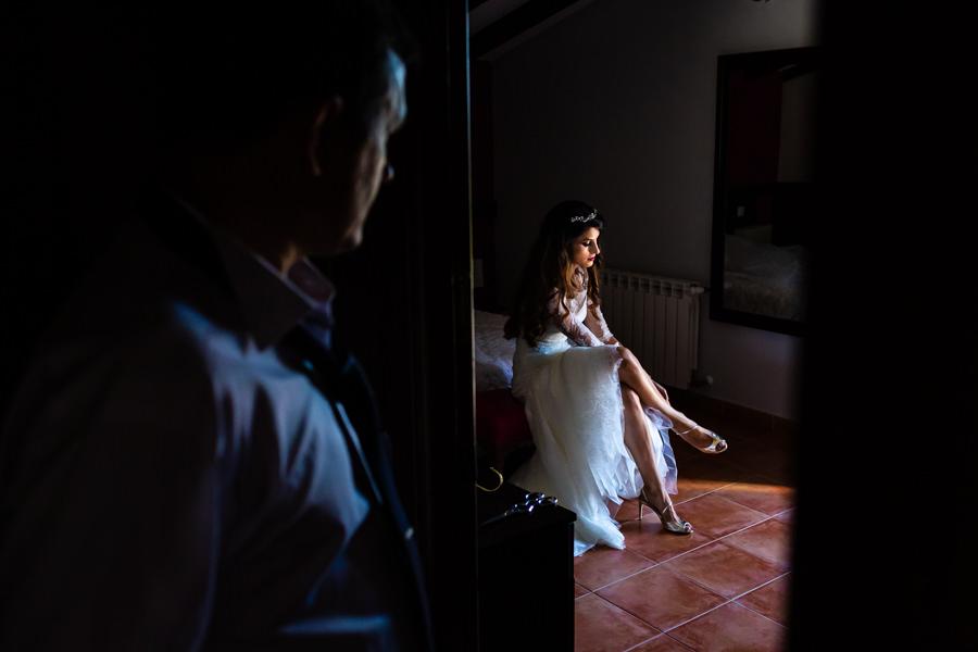 Boda en Hervás de Yolanda e Ignacio, foto realizada por el fotógrafo de bodas en Cáceres Johnny García. Yolanda se pone los zapatos mientras es observada por su padre.