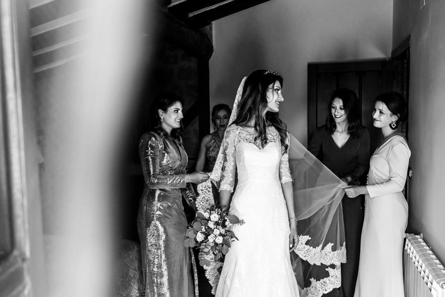 Boda en Hervás de Yolanda e Ignacio, foto realizada por el fotógrafo de bodas en Cáceres Johnny García. Familiares y amigas ayudan a la novia a vestirse.