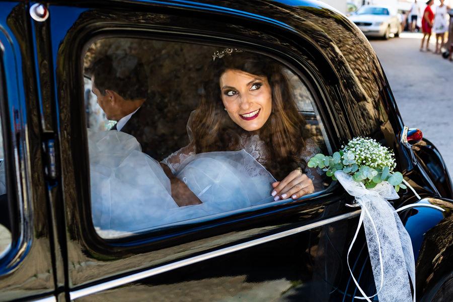 Boda en Hervás de Yolanda e Ignacio, foto realizada por el fotógrafo de bodas en Cáceres Johnny García. Yolanda observa desde el interior del coche a su llegada a la ceremonia.