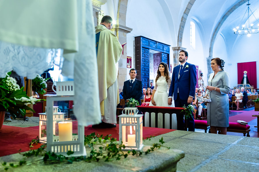 Boda en Hervás de Yolanda e Ignacio, foto realizada por el fotógrafo de bodas en Cáceres Johnny García. Los novios escuchan al sacerdote.
