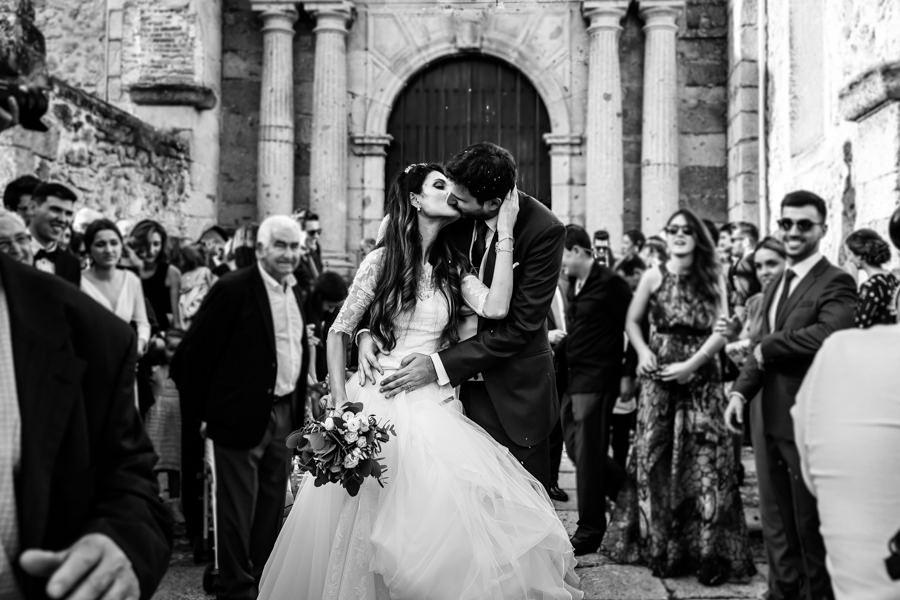 Boda en Hervás de Yolanda e Ignacio, foto realizada por el fotógrafo de bodas en Cáceres Johnny García. Los novios se besan en la puerta de la iglesia junto a todos sus invitados.