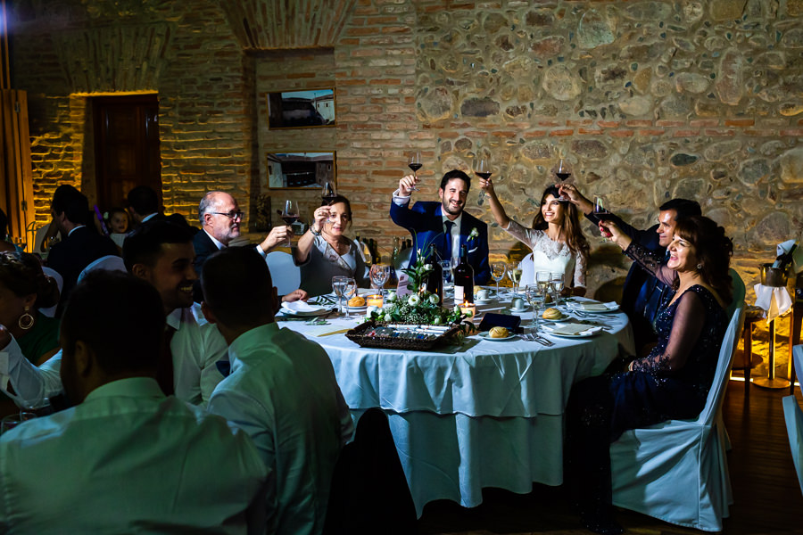 Boda en Hervás de Yolanda e Ignacio, foto realizada por el fotógrafo de bodas en Cáceres Johnny García. Los novios brindan con sus invitados desde la mesa nupcial.