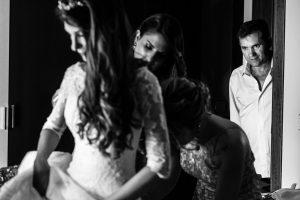 Boda en Hervás de Yolanda e Ignacio, foto realizada por el fotógrafo de bodas en Cáceres Johnny García. La hermana de la novia la ayuda con los botones del vestido.