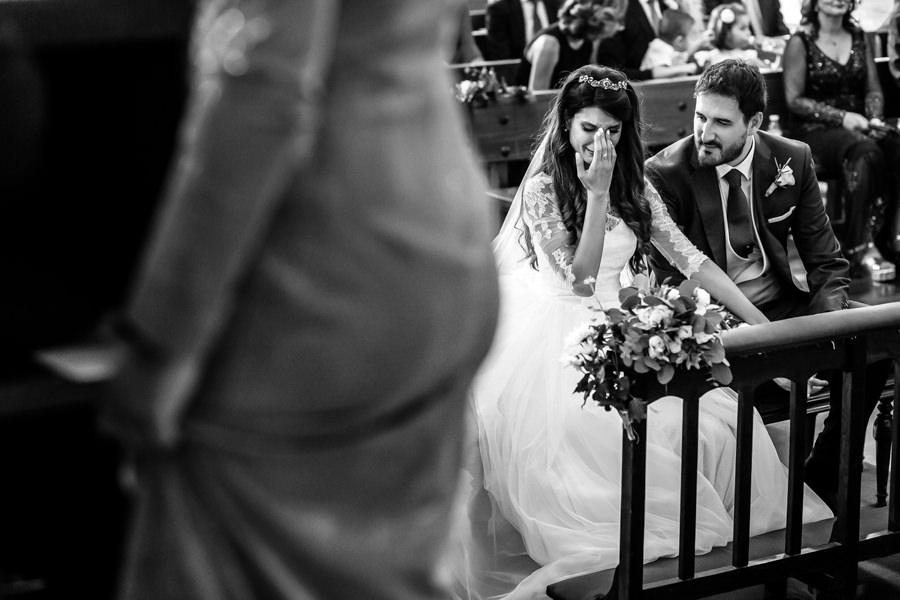 Boda en Hervás de Yolanda e Ignacio, foto realizada por el fotógrafo de bodas en Cáceres Johnny García. La novia se emociona escuchando a sus hermanos en la ceremonia.