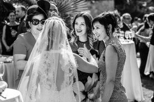 Boda en Puerto de Béjar de Susana y Benjamín, realizada por el fotógrafo de bodas en Guijuelo Johnny García. la novia charla con unas amigas.